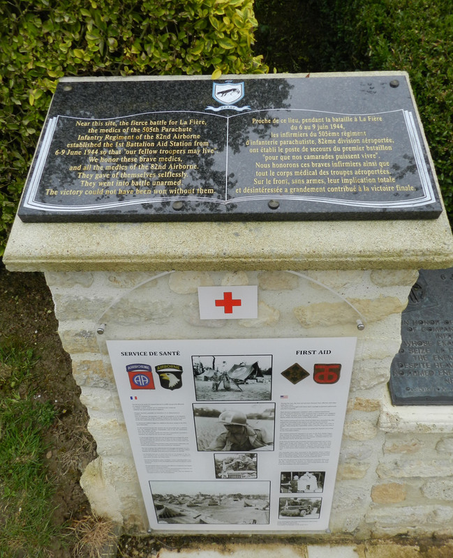 Conjunto memorial compuesto por varias placas conmemorativas, paneles descriptivos y una estatua de un Iron Mike en el puente sobre el río Merderet
